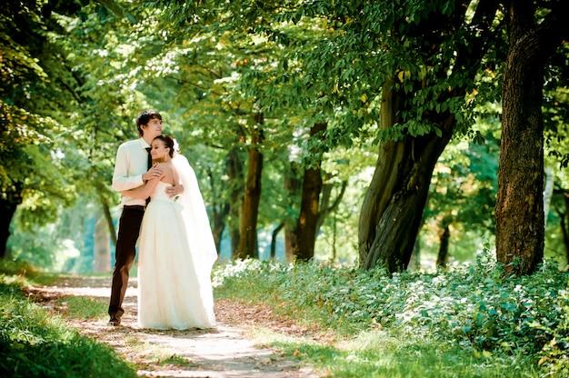 Счастливая невеста и жених на прогулке в красивом лесу