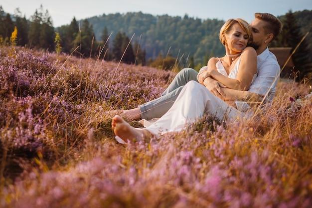 Счастливый жених и невеста позируют на фиолетовом поле