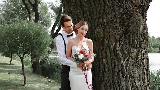 Счастливая невеста и жених, стоя возле большого дерева