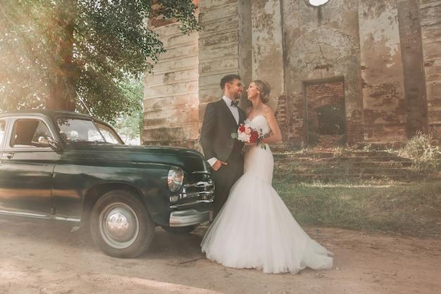 Счастливая невеста и жених, стоя возле старинного автомобиля