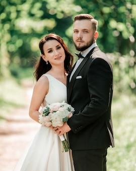 Счастливая невеста и жених, стоя под свадебной аркой. события и традиции