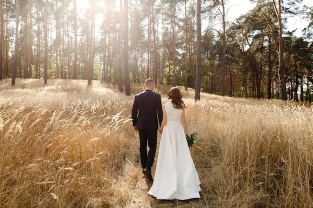 Счастливый жених и невеста, ходить в поле колосья пшеницы в солнечный день. молодожены держатся за руки. день свадьбы на открытом воздухе летом. свадебная пара, наслаждающаяся романтичным моментом. романтическое свидание на природе