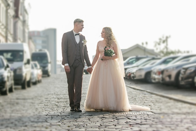 Счастливая невеста и жених, прогулки по улице города. фото с копией пространства