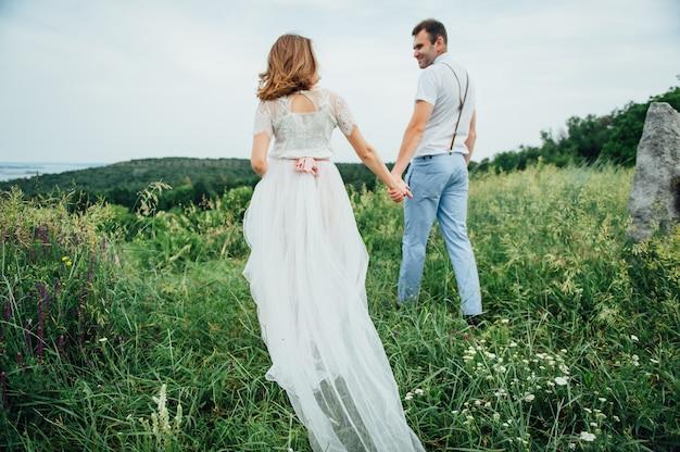 緑の芝生の上を歩いて幸せな新郎新婦