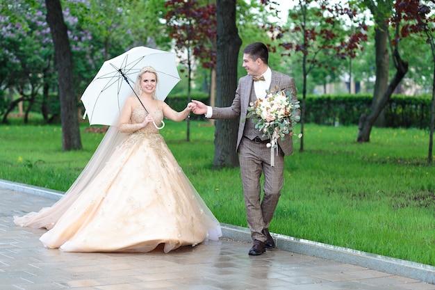 행복 한 신부 그리고 공원에서 여름에 빗 속에서 하얀 우산으로 신랑. 야외 결혼식.