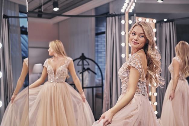 행복한 신부. 웨딩 드레스를 입고 신부 가게의 거울 앞에 서서 웃고 있는 아름다운 젊은 여성