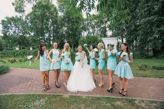 A happy bride dances surrounded by her friends in identical dresses at the wedding.