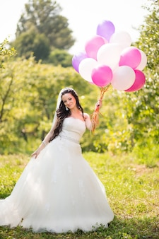 Happy bride in dress wit colorful ballons in green park