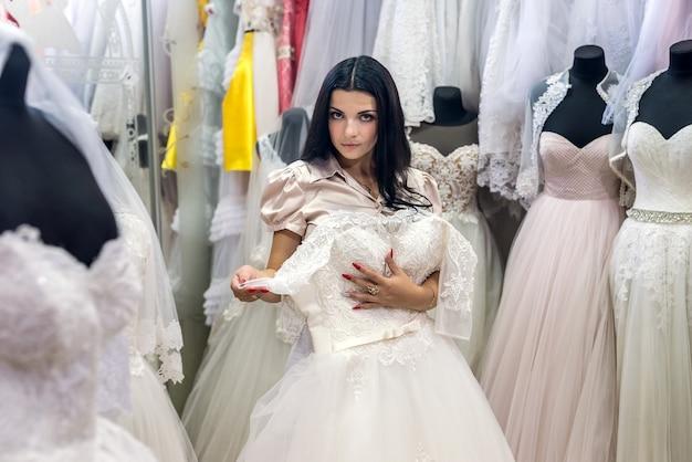 Happy bride fitting wedding dress in salon
