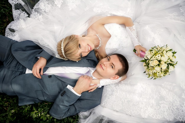 Happy bride and groom are lying on green grass