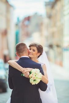 Happy bride and groom dancing on street