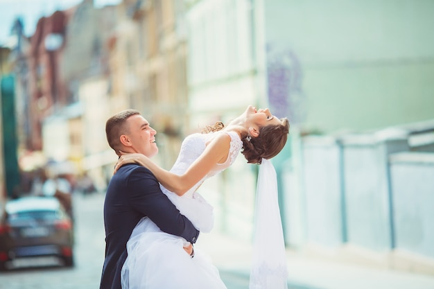 Happy bride and groom dancing on a street