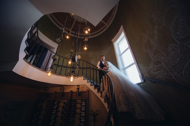 Happy bride and groom kissing and hugging on a spiral staircase. portrait of loving newlyweds in a beautiful interior. wedding day. smiling just married couple