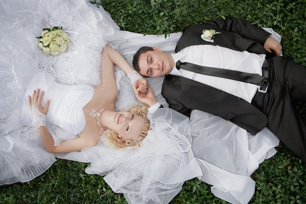 Happy bride and groom lying on green grass