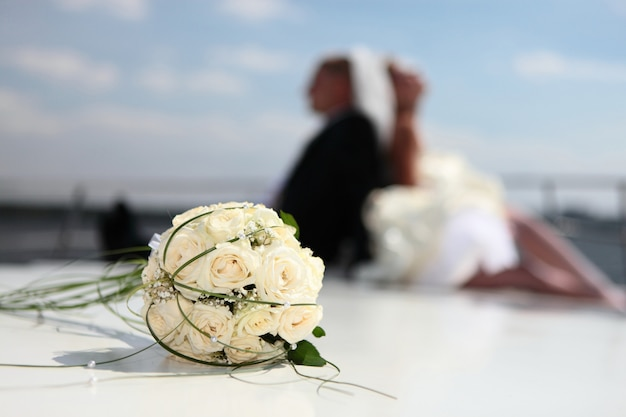 Happy bride and  groom sit on the yacht with a wedding bouquet