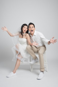 Happy bride and groom sitting on a chair