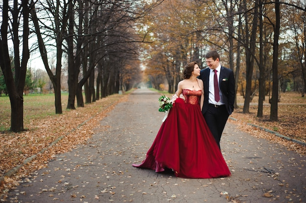 Happy bride and groom walking in the autumn forest.