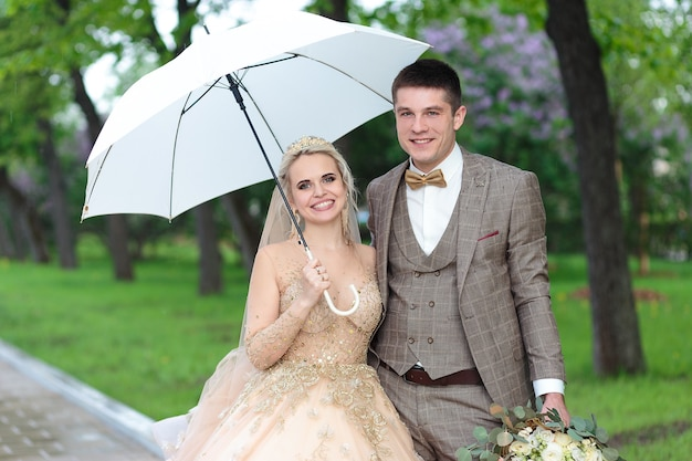 Happy bride and groom with a white umbrella in the rain, in the summer in the park. open-air wedding.