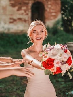 彼女の友人に結婚式の花束を渡す幸せな花嫁。休日と伝統