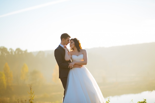 Happy bride and handsome brunette beautiful bride in a white dress, embrace under the arc