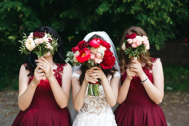 Happy bride and her friends hold beautiful flowers