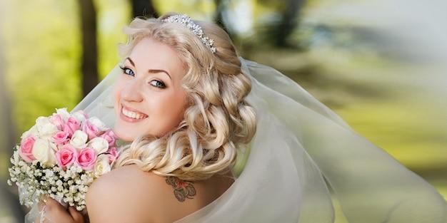 Счастливая невеста в вуали, держа ее букет, глядя на камеру в сельской местности