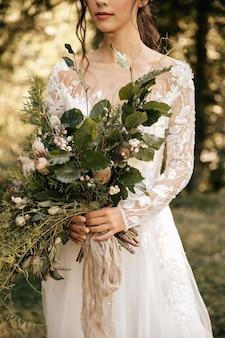 美しいウェディングブーケと白いウェディングドレスの幸せな花嫁