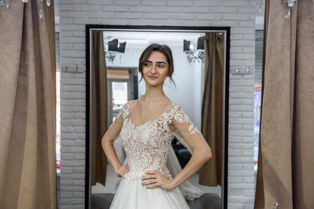ウェディングドレスでポーズをとってサロンで幸せな花嫁