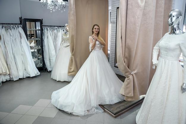 サロンに立っているウェディングドレスの幸せな花嫁