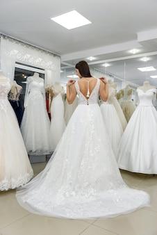 Счастливая невеста в свадебном платье, стоя в салоне