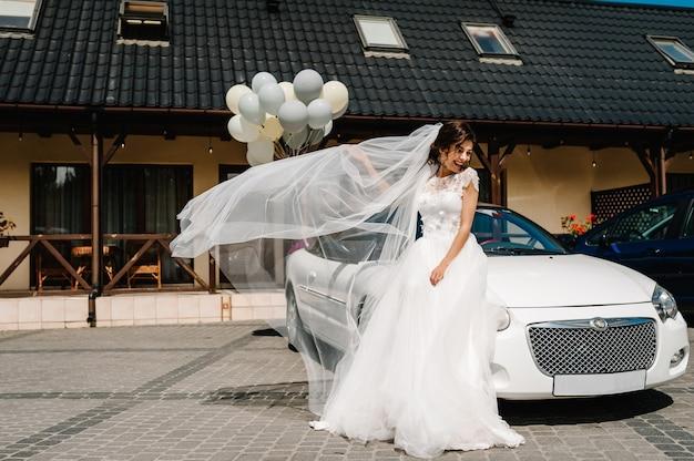 Счастливая невеста возле дома за городом и кабриолет