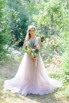Happy bride in a pink wedding dress. the girl holds a wedding bouquet in her hands. boho style wedding ceremony in the forest.