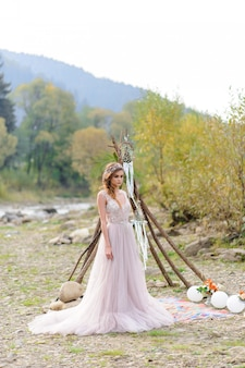 Happy bride in a pink wedding dress. the girl holds a wedding bouquet in her hands. boho style wedding ceremony near the river.