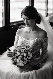 Happy bride sitting near window and look at the wedding bouquet. beautiful young woman in a white dress with a bouquet of flowers.