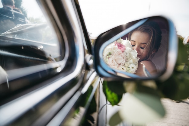 Happy bride sniffs flowers in the car