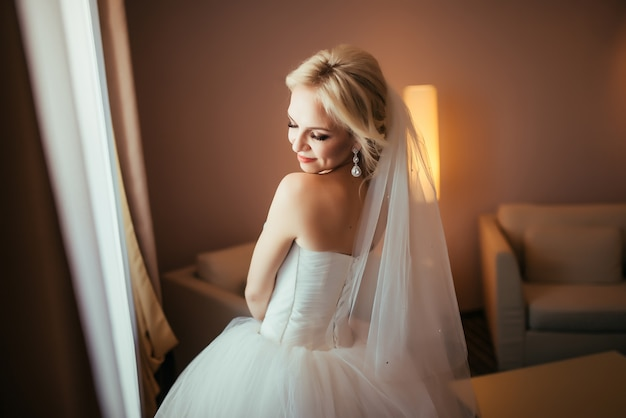 Happy bride standing with closed eyes, getting pleasure from future wedding.