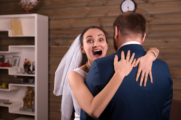 Happy bride in veil embracing groom in suit after he made marriage proposal