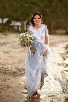 青いウェディングドレスのウェディングブーケとビーチに沿って歩く幸せな花嫁