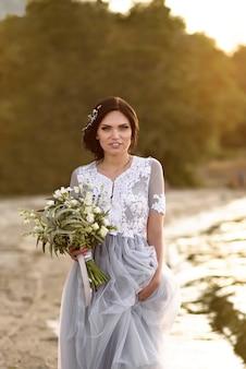 夕暮れ時の結婚式の花束とビーチに沿って歩く幸せな花嫁