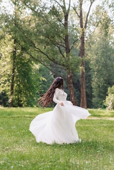 Happy bride in a white dress whirls on her wedding day in a clearing in the park in summer