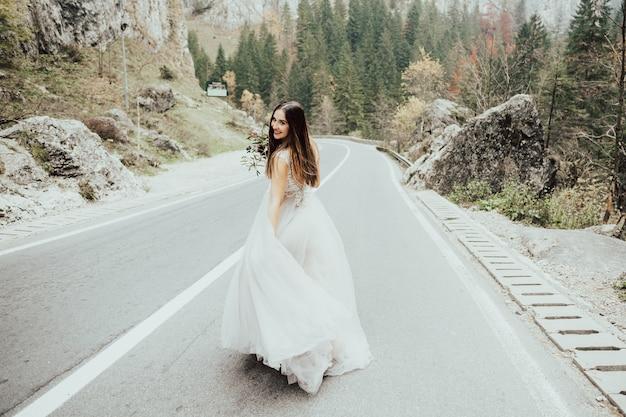 山道を歩いている花の花束を持つ幸せな花嫁。