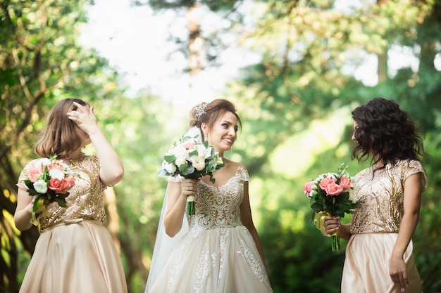 Happy bride with bridesmaid hold bouquets and have fun outside. background of nature