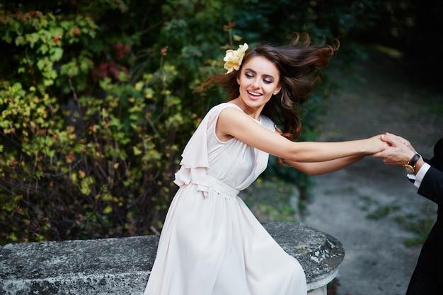 Счастливая невеста с длинными вьющимися волосами в свадебном платье в парке, свадебное фото, портрет, фото в движении.