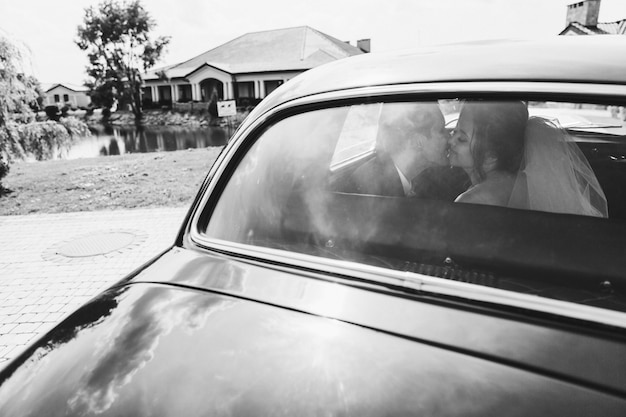 Happy brides are kissing in the car