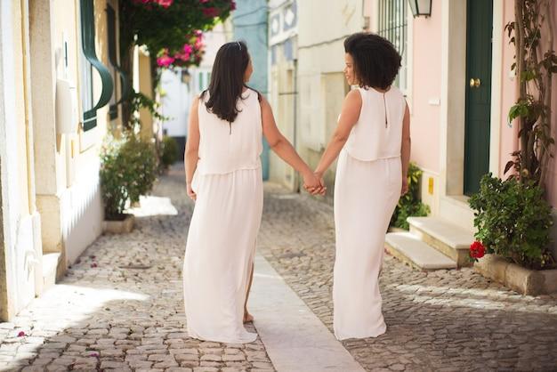 Happy brides going down street
