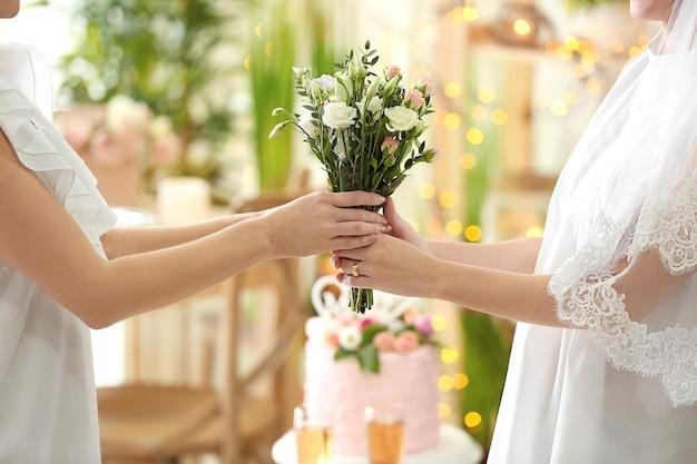 レズビアンの結婚式で美しい花の花束を保持している幸せな花嫁