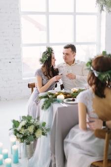 幸せな花嫁介添人と新郎の結婚式のテーブルでシャンパンを飲む
