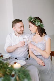 松の花輪と新郎の結婚式のテーブルで幸せな花嫁介添人はシャンパンを飲む
