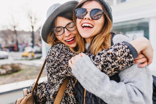 街の通りでハグする2人のスタイリッシュな女性の幸せな明るくポジティブな瞬間。クローズアップの肖像画面白い楽しいうれしそうな若い女性が楽しんで、笑顔、素敵な瞬間、親友。