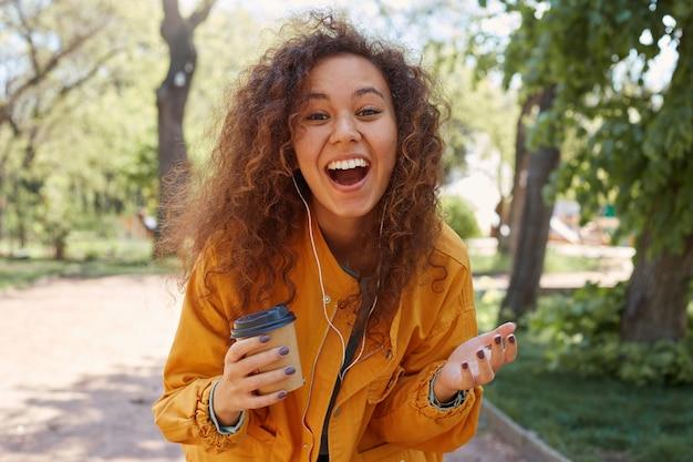 Felice ragazza riccia e riccia dalla pelle scura, che indossa una giacca gialla, tiene in mano una tazza di caffè, si gode il tempo nel parco e ride con battute divertenti, guardando.